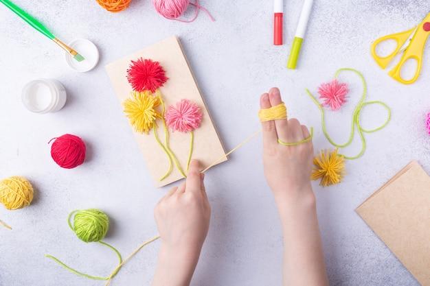 Artesanato de papel para a marcha do dia das mães ou aniversário de criança pequena fazendo um buquê de flores de papel colorido e bolas de tricô coloridas para a mãe ideia de presente simples visualizar espaço de cópia superior foto de alta qualidade