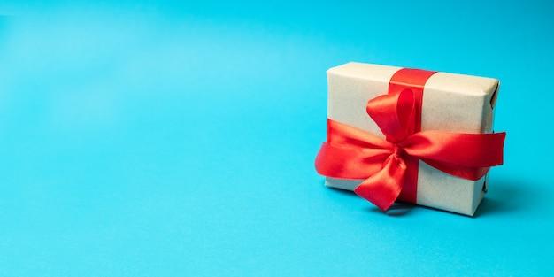 Artesanato de papel presente com fita vermelha sobre fundo azul. tiro quadrado