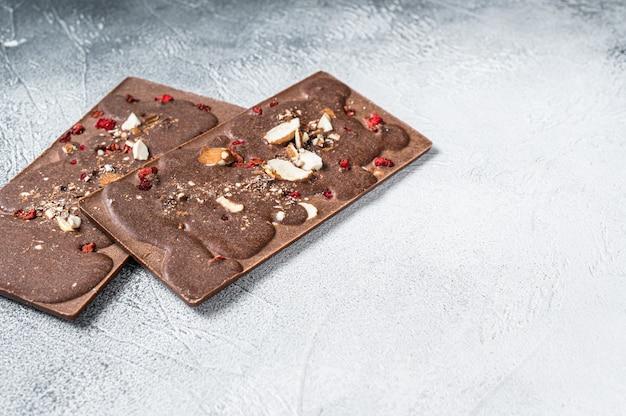 Artesanato em barras de chocolate caseiras na mesa da cozinha. fundo branco. vista do topo. copie o espaço.