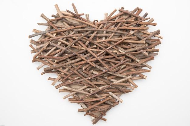 Artesanato em forma de coração feito de pequeno galho seco, sobre fundo branco