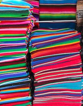 Artesanato mexicano colorido poncho empilhados