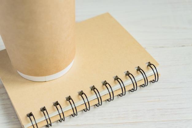 Artesanato papel copo de café e caderno diário com espaço de cópia na mesa de madeira