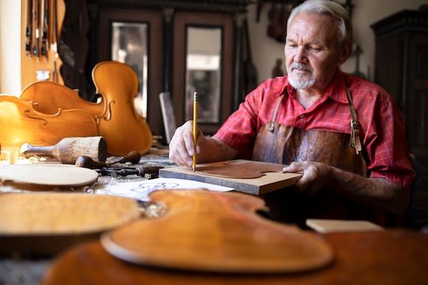 Artesão carpinteiro sênior fazendo violino em sua antiga oficina de carpinteiro