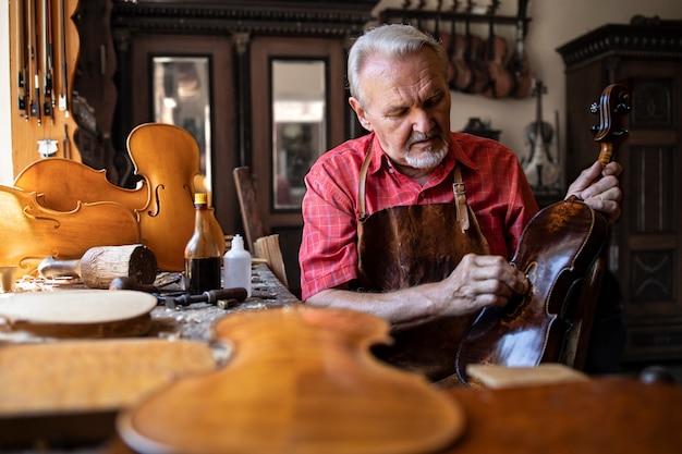 Artesão carpinteiro sênior polindo instrumento de violino em sua oficina de carpinteiro.