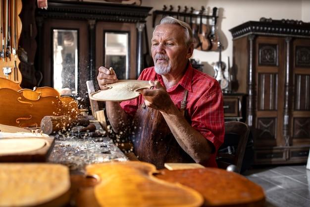 Artesão carpinteiro sênior trabalhando com madeira nobre na oficina e soprando serragem