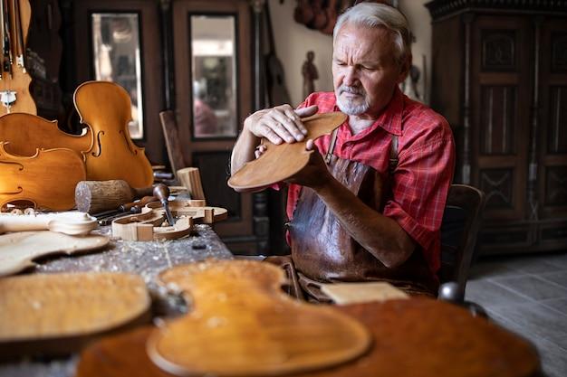 Artesão carpinteiro sênior verificando a qualidade do produto de madeira