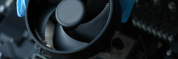 Artesão com luvas instalando o cooler na placa de vídeo close-up