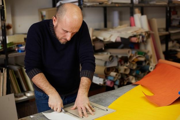 Artesão cortando couro com cortador em oficina Foto Premium