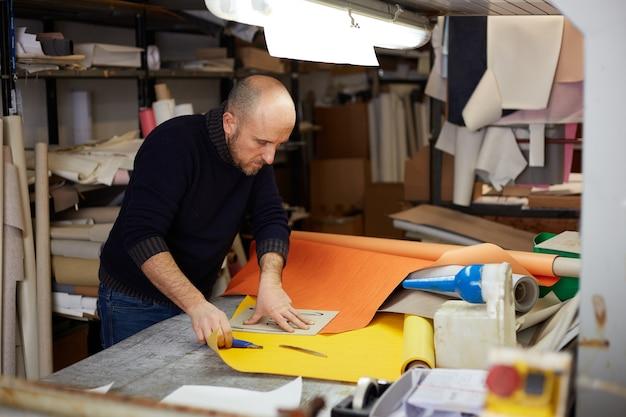 Artesão cortando couro com cortador em oficina