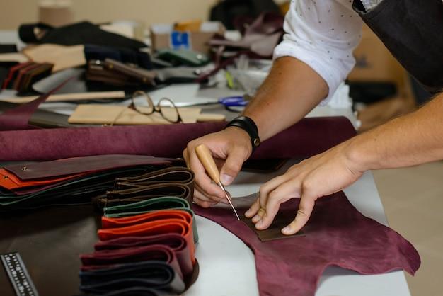 Artesão de bolsa de couro no trabalho em uma oficina