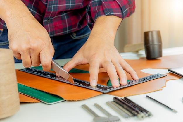 Artesão de couro com camisa vermelha trabalhando medindo e cortando em couro genuíno