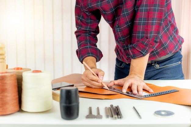 Artesão de couro com camisa vermelha trabalhando medindo e escrevendo em couro genuíno