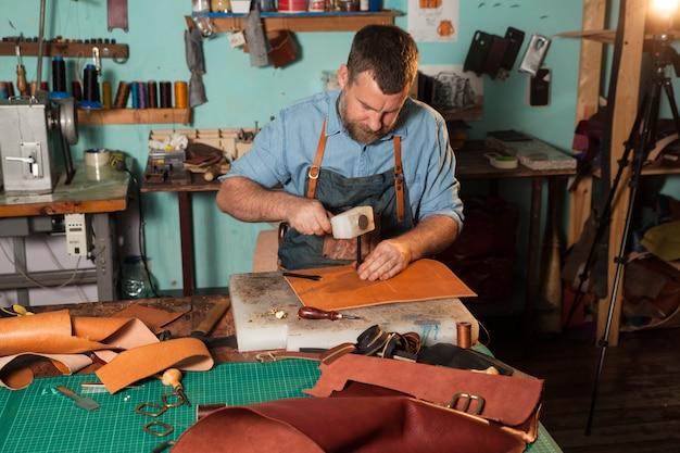 Artesão de couro que trabalha com couro natural usando o martelo. mestre da bolsa no trabalho na oficina local.