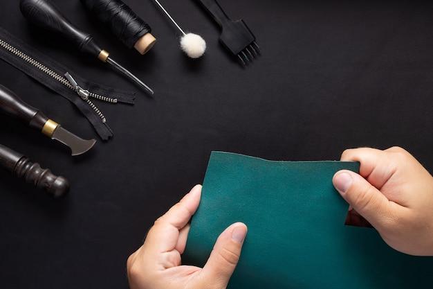 Artesão de couro segurando uma amostra de couro verde e um kit de ferramentas
