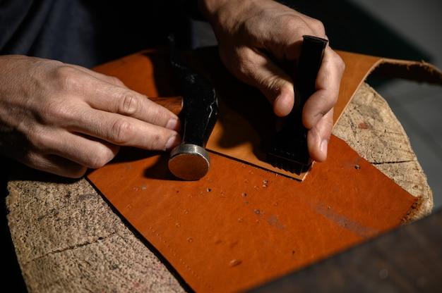 Artesão de couro trabalha na loja de curtumes
