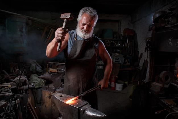 Artesão de ferreiro em avental trabalha na loja de ferreiro