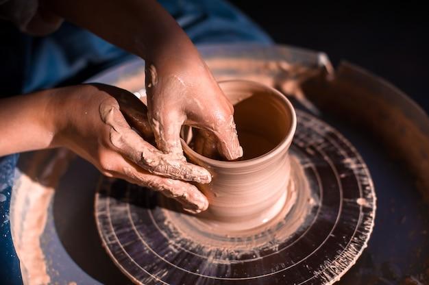 Artesão de oleiro sentado em um banco com uma roda de oleiro e fazendo panela de barro