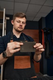 Artesão em couro confere um produto em uma oficina, empresa familiar de costura em couro, artesanato, pequenas e médias empresas.