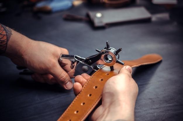 Artesão executa couro trabalhando para um novo produto em sua loja de bronzeamento