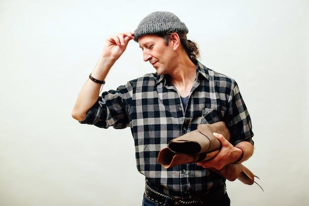 Artesão mantém conjunto de couro em sua oficina. conceito de negócios e empreendedor. mestre tem idéia para novos produtos de couro. pequenos negócios