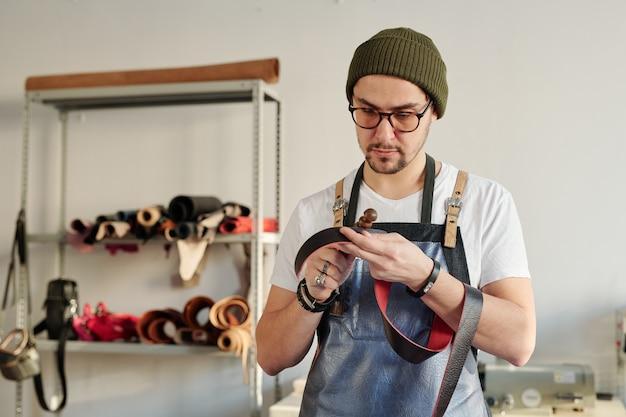 Artesão profissional em roupas de trabalho segurando um cinto de couro vermelho e uma ferramenta de mão de madeira enquanto trabalhava em um novo item para o cliente