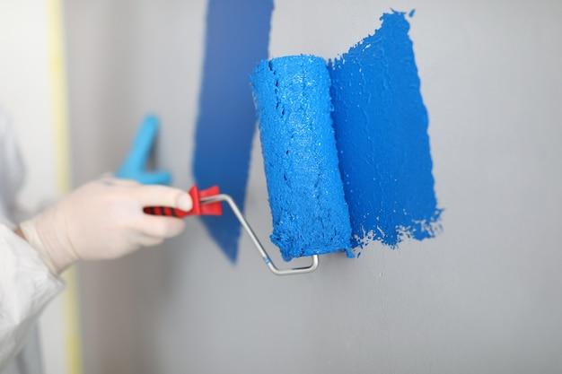 Artesão segura o rolo e pinta a parede branca de azul. conceito de serviços de pintor
