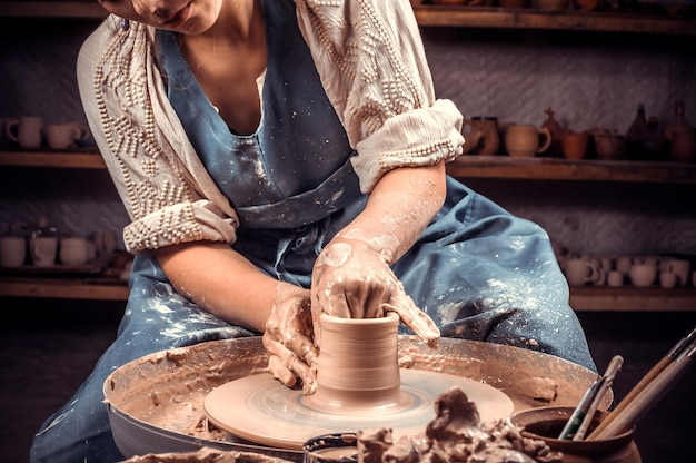 Artesão sentado em um banco com roda de oleiro e fazendo panela de barro
