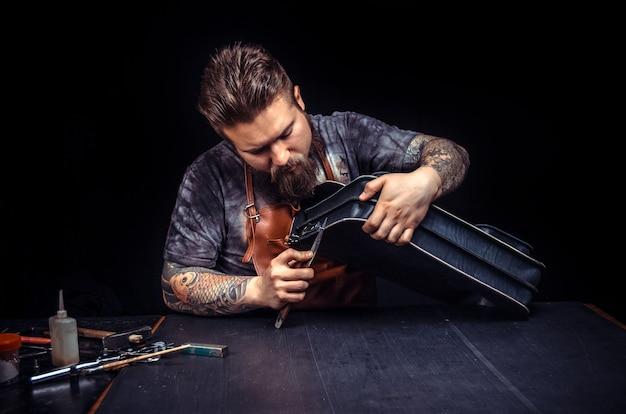 Artesão trabalhando com couro cortando artigos de couro