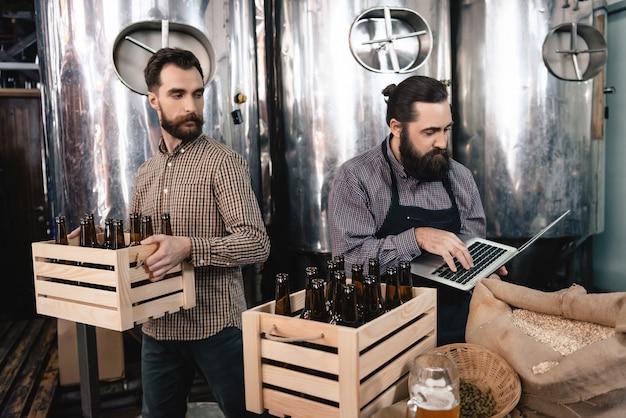 Artesãos contando microcervejaria de garrafas de cerveja.