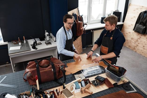 Artesãos de couro trabalhando fazendo medições em padrões na mesa no estúdio de oficina.