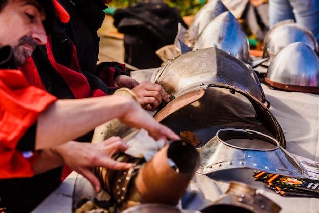 Artesãos disfarçados de era medieval, polindo armaduras sujas para limpá-los.