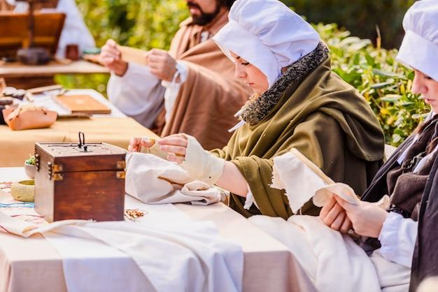 Artesãos disfarçados em épocas medievais exibindo artesanato antigo em uma exposição de um festival.