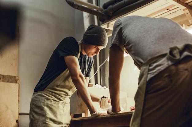 Artesãos fazendo medições na bancada