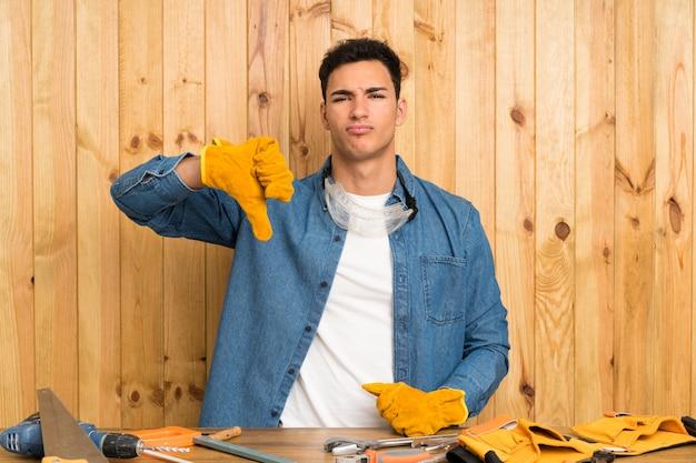 Artesãos homem sobre madeira mostrando o polegar baixo sinal