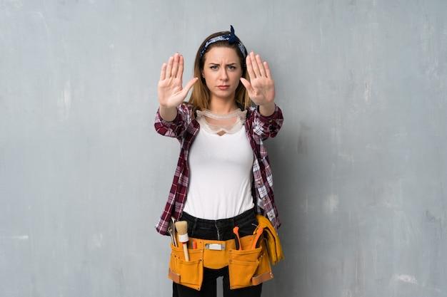 Artesãos ou mulher eletricista fazendo gesto de parada e decepcionado