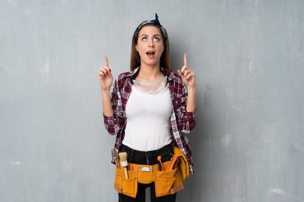 Artesãos ou mulher eletricista surpreso e apontando para cima
