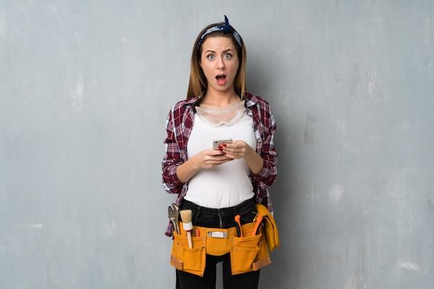 Artesãos ou mulher eletricista surpreso e enviando uma mensagem