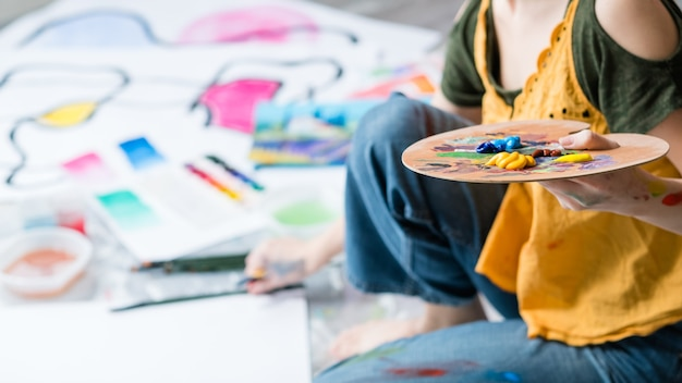 Arteterapia e lazer. foto recortada de uma senhora usando paleta de tinta acrílica, criando obras de arte