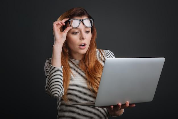 Artigo chocante. mulher expressiva e elegante segurando os óculos enquanto usa o computador e parecendo surpresa