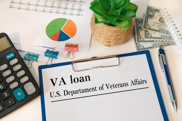 Artigo com empréstimo va - departamento de assuntos de veteranos dos eua na mesa, calculadora e óculos