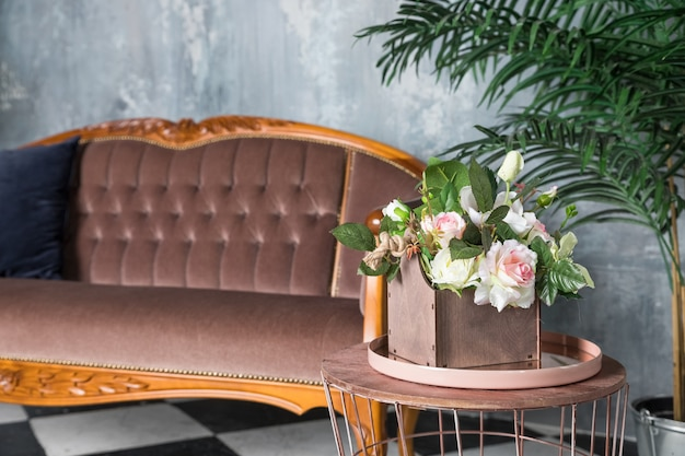 Artigo decorativo interior em casa na mesa com frasco de vidro e flores secas, vela. almofadas coloridas no sofá cinza. sala de estar com sofá marrom. interior do apartamento loft com sofá