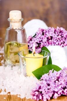 Artigos de banho e spa (toalha, sal, óleo, lilás, vela) sobre fundo de madeira