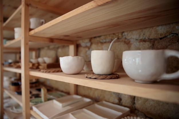 Artigos de cerâmica feitos à mão em prateleiras de madeira