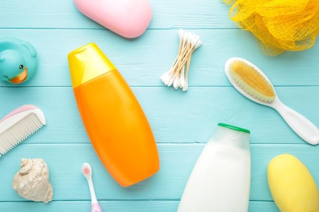 Artigos de higiene pessoal bebê na parede azul. gel de banho de bebê. vista do topo