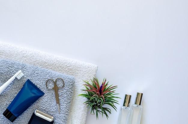 Artigos de higiene pessoal masculinos no estilo de vida moderno em toalhas com planta de ar tillandsia em fundo branco.