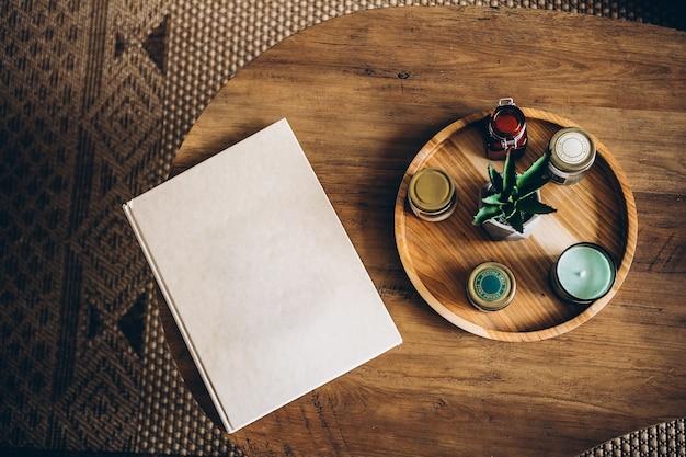 Artigos de interior: velas, sachês aromáticos, flor de babosa em um suporte redondo de madeira sobre uma mesa de madeira. livro de capa dura com conceito de casa aconchegante