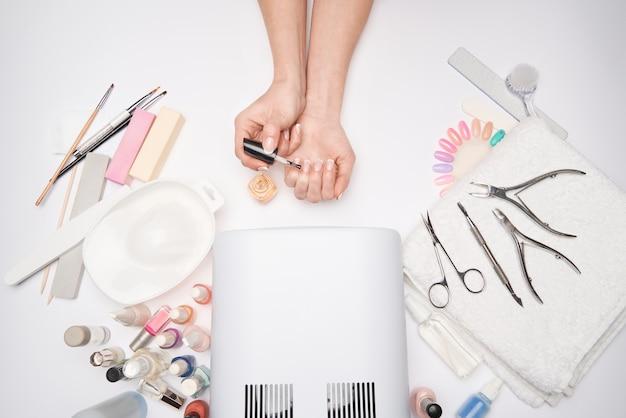 Artigos de manicure e pedicure - lâmpada de secagem de esmalte, lixa de unha, tesouras e pincéis sobre superfície clara.
