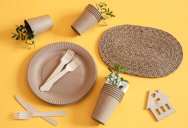 Artigos de mesa em papel reciclável ecológicos e elegantes. caixas de papel para comida, pratos e talheres de amido de milho em um fundo laranja de tendência.