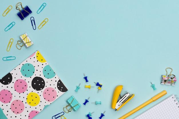 Artigos de papelaria. artigos coloridos para estudo e trabalho no escritório, sobre um fundo azul. de volta à escola. postura plana com espaço de cópia.