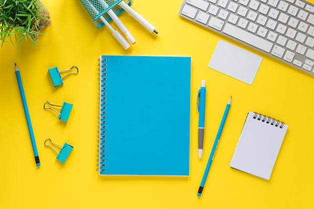 Artigos de papelaria azuis com teclado e bloco de notas em espiral no pano de fundo amarelo
